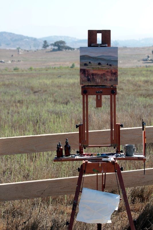 A view of the painting on the easel in the unfinished state.